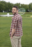 Man in checkered shirt holding badminton racquet and smiling at camera Stock Images