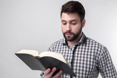 A man in a checkered shirt holding a black book on a light background. Bearded student. Stock Images