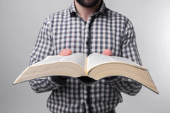 A man in a checkered shirt holding a black book on a light background. Bearded student. Stock Photos