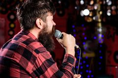 Man in checkered shirt holds microphone, singing song, karaoke club background. Guy likes to sing in dark karaoke hall. Rock singer concept. Musician with Royalty Free Stock Photo