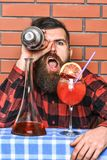 Man in checkered shirt holds shaker in front of eye, brick wall background. Barman and cocktails concept. Barman with. Long beard and stylish hair with cheerful Royalty Free Stock Photo