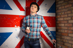 Man in Checkered Shirt and Jeans In Front UK Flag Royalty Free Stock Photography