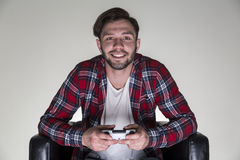 Man in a checkered shirt sitting in a leather armchair and holding a video game controller. Portrait of a cheerful young man in a checkered shirt sitting in a Royalty Free Stock Photo