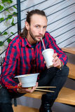 Man in checkered shirt sitting on stairs and eating asian food Royalty Free Stock Photography