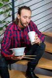 Man in checkered shirt sitting on stairs and eating asian food Stock Photography