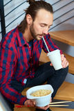 Man in checkered shirt sitting on stairs and eating asian food Stock Images
