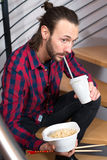 Man in checkered shirt sitting on stairs and eating asian food Stock Photos