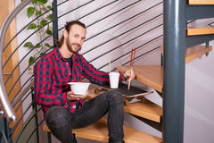 Man in checkered shirt sitting on stairs and eating asian food Stock Photo