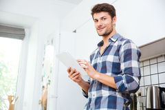 Man in checkered shirt using tablet on the kitchen Royalty Free Stock Image