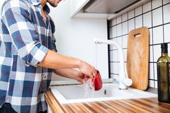Man in checkered shirt washing dishes on the kitchen Royalty Free Stock Photography