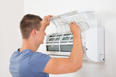 Man Checking Air Conditioner Royalty Free Stock Images