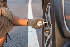 Man checking air pressure and filling air in the tires of his  Royalty Free Stock Images