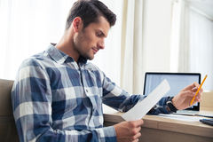 Man checking bills at home Stock Image