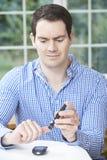 Man Checking Blood Sugar Level At Home Stock Photo