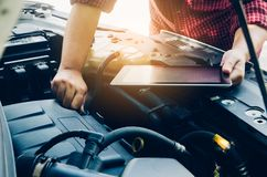 Man checking on a car engine and hold tablet search for data.  Stock Photography