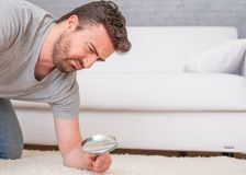 Man checking for carpet dust mites and bug parasites stock photos