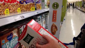 Man checking cereal ingredient in grocery store stock footage