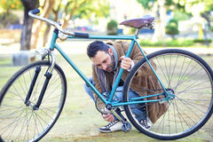Man checking the chain an bicycle Stock Photography