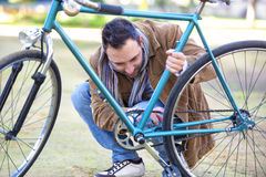 Man checking the chain an bicycle Stock Photo