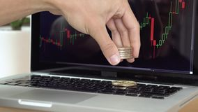 4k resolution of a man playing with Bitcoin coins, counting them with cryptocurrency chart on a laptop