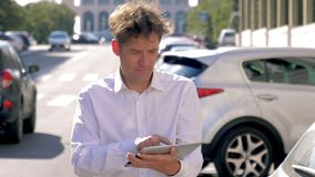Man checking email on tablet in street of city with traffic slow motion stock video footage