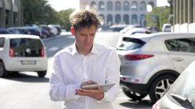 Man checking email on tablet in street of city with traffic slow motion stock footage