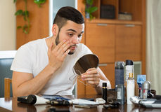 Man checking eyelid in a mirror. Handsome man checking his eyelid in a mirror Royalty Free Stock Photos