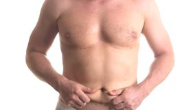 Man checking fat on his stomach. Closeup stomach of man in shorts checking his belly and showing thumbs down isolated over white background stock footage