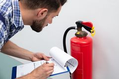 Man Checking Fire Extinguisher Writing On Document stock image