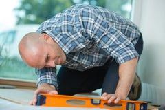 Man checking flooring level. Man checking flooring is level Stock Image