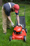 Man checking gas powered lawn mower stock photos