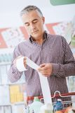 Man checking a grocery receipt stock photo