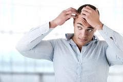 Man Checking Hairline. In a blue background stock photography
