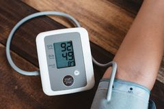 Man checking his blood pressure using electronic blood pressure monitor or sphygmomanometer on a wooden table stock images