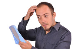 Man checking his hair loss in the mirror. Young attractive guy is checking his hair loss in the mirror. White background Stock Images