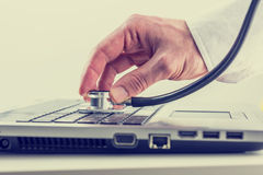Man checking his laptop with a stethoscope. Man checking his laptop computer with a stethoscope holding the disk over the keyboard as he looks for viruses and Royalty Free Stock Photo