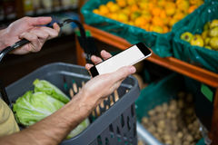 Man checking his mobile phone while buying vegetables Royalty Free Stock Photo