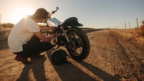 Man checking his motorcycle on country road royalty free stock photography