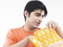 Man checking his shopping bag. Asian male of indian origin looking through his shopping bag Royalty Free Stock Photo