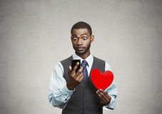 Man checking his smart phone, holding red heart Royalty Free Stock Photography