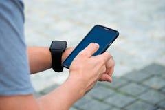 Man checking his smartwatch outdoors. High angle shot. Stock Photos