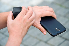 Man checking his smartwatch outdoors. High angle shot. Stock Image