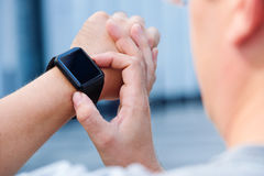 Man checking his smartwatch outdoors. High angle shot. Stock Photography