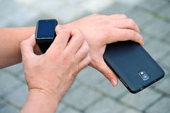 Man checking his smartwatch outdoors. High angle shot. Royalty Free Stock Photography