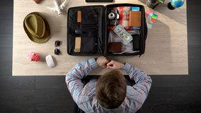 Man checking his suitcase before travel, taking money and documents, top view. Stock photo Stock Image