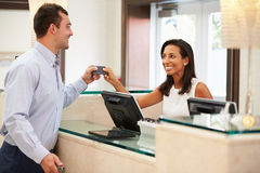 Man Checking In At Hotel Reception Stock Image