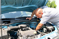 Man checking inside hood of car Stock Images
