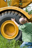 Man checking large tire. Man inspecting large tire for defects stock photos