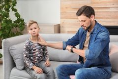 Man checking little boy`s pulse with fingers. At home royalty free stock photo