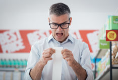 Man checking a long receipt Royalty Free Stock Photography